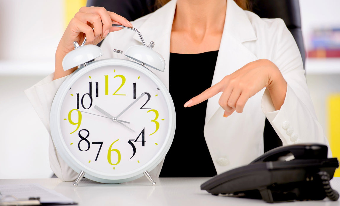Woman pointing at clock - Working time regulations