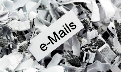 Black and white image of paper with e-mails written on it on background of shredded paper