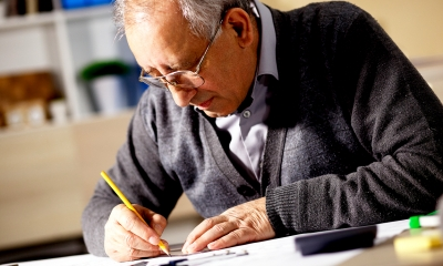 Older man in glasses writing on paper answering his employees questions