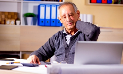 Older man holding his neck while sitting down at his desk