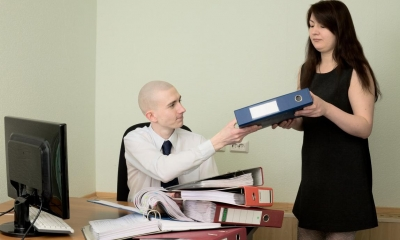Female bookkeeper giving a man a blue folder with other folders already on the table