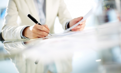Close up of a man holding a pen and signing a contract