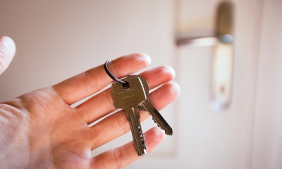 Hand holding keys to door of newly purchased business