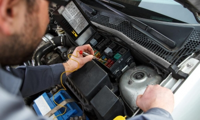 Mechanic improving car alarm capabilities under a bonnet of a car