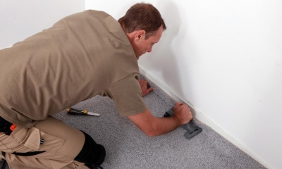 Male carpet fitter fitting carpet onto the floor