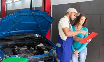 Car mechanic and customer stood next to car