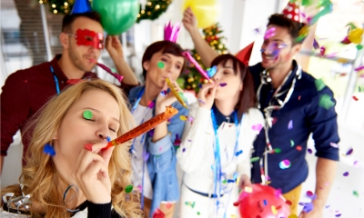 Workmates celebrate with confetti, balloons and party hats - the office Christmas party.