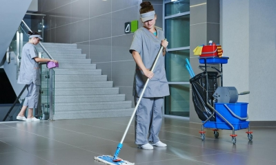 Two female contract cleaners in grey uniforms cleaning cleaning the stairway of a building
