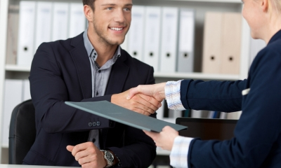 A business man and woman shake hands while handing over a contract