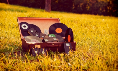Suitcase lying in a field containing multiple vinyl records