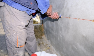 Male damp proofer in work gear filling in holes in a wall using a plastic bottle