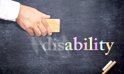 Man rubbing out 'disability' written in multicoloured chalk on a blakcboard