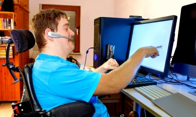 Disabled man in a special chair touching the computer screen at the workplace