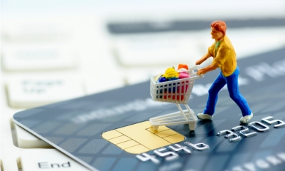 Toy man with shopping trolley on a black credit card on a keyboard