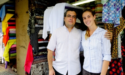 Man and a woman linking arms in front of a family textile business
