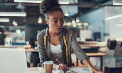 Woman wearing glasses stood at a desk holding a pen with a coffee in front of her