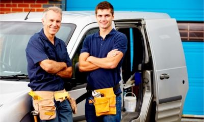 A father and son stand next the the family business van