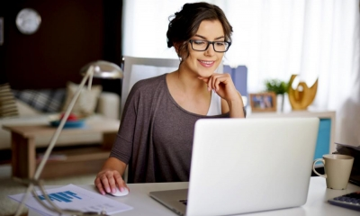 Woman in glasses sat at a desk using her laptop whilst working from home