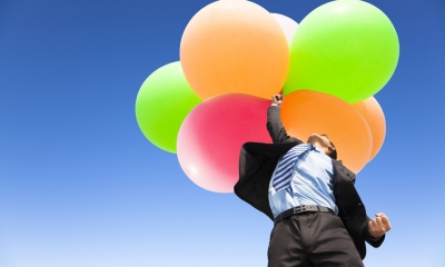 Businessman floating into the air holding balloons
