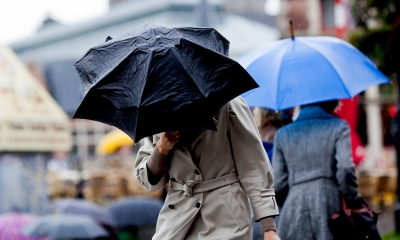 Woman walking to work in bad weather while holding a black umbrella