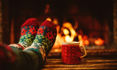 Person wearing woolly socks with their feet up by the fire while on holiday