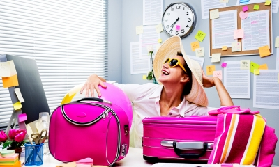 Woman wearing a beach hat and glasses with pink suitcases on her desk
