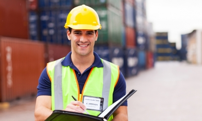 Warehouse worker with clipboard in front of multiple shipping containers