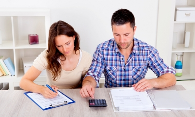 Two parents calculating their maternity and paternity pay