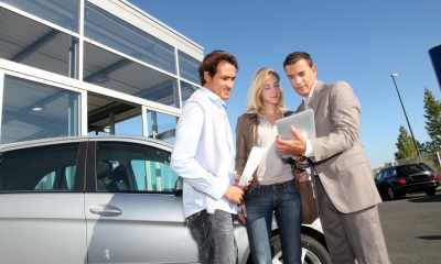 A motor dealer showing a legal contract to a couple at a motor dealership