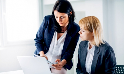 Female business executive explains something to another seated female business executive