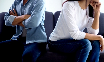 A divorcing couple sit apart on a sofa and avoid eye contact.