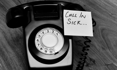 'CALL IN SICK' written on a post-it note on a telephone representing online absence