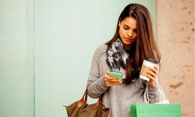 Young woman using her smartphone and drinking coffee while doing some shopping in a mall
