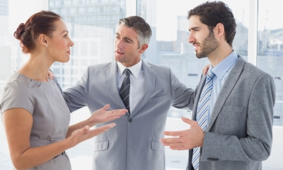 Man in grey suit resolving a dispute between two employees