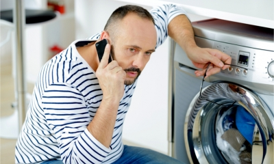 Engineer on phone next to faulty washing machine