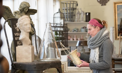 Woman holding vase in antique shop with antique items in background