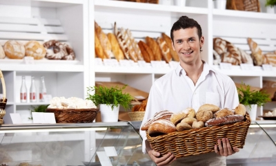 Man holding basket of baked goods in bakery