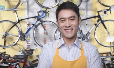 Man in shirt and yellow apron in front of multiple bicycles in bicycle shop