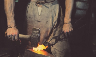 Blacksmith hammering hot metal in dark room