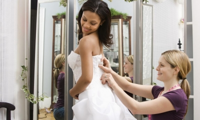 Woman fitting wedding dress onto bride in bridal shop