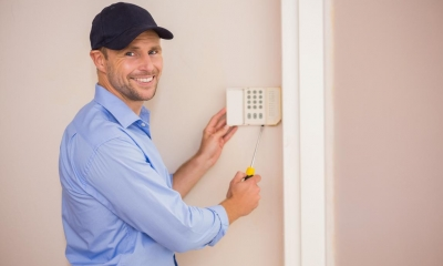 Man in blue shirt and cap fitting alarm onto a wall