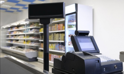 Black cash register with refrigerated products in background