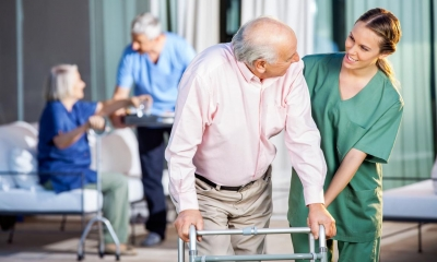 Carer helping old man walk with his frame with two people in background