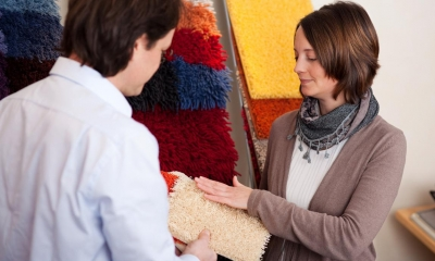 Woman feeling beige carpet sample from employee in carpet shop