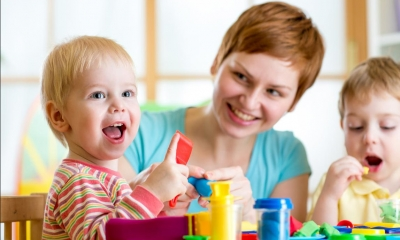 Woman looking after two children playing with toys