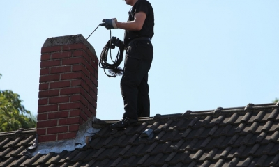 Man on roof sweeping a chimney on a sunny day
