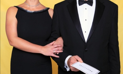 Man in black suit and woman in black dress with yellow background