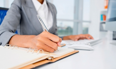 Female company administrator in a grey suit writing on a notepad