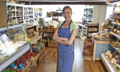 Woman in blue and white striped apron in delicatessen