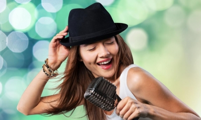 Woman in top hat singing into microphone